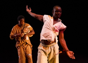 "Souleymane Badolo with Cynthia Oliver Boom!, Barack, and Buudou, Badoo, Badolo New York, New York Live Arts 22 April 2013 NYLA bio page www.newyorklivearts.org Dance of Sadness The nineteenth-century choreographer August Bournonville wrote of dance that it was ""essentially an expression of joy, a desire to follow the rhythms of the music."" The body, especially when moving to the accompaniment of music, conveys this feeling of exultation, of momentary transcendence. This is paradoxically true even when the underlying feeling being expressed is something other than joy. Then, the audience experiences both emotions at once: the joy of the body in motion, colored by whatever emotion is being evoked through the choreography. The greater the dancer, the more stirring the joy. Or so I thought, until I saw Souleymane Badolo dancing two solos of his own making, Barack and Buudou, Badoo, Badolo, at New York Live Arts. Badolo, who was born and raised in Burkina Faso and who performed for several years in a company specializing in traditional African dance (DAMA), is a marvelously articulate, muscular, dancer. He dances with his whole body, his head, his feet, his back, his chest, even the tips of his fingers. His movements are full of detail and texture and sensuality, peppered with sudden changes of tempo and force. And yet, at least in these works, his dancing, though beautiful and sometimes outwardly euphoric, expresses almost no joy. It is as if it had been steeped in a deep sadness, a sadness that cannot be washed away. By dancing, he seems to will himself to pleasure. He never quite gets there.   The evening opened with a short work, Boom!, by another choreographer, Cynthia Oliver, a duet for herself and the younger Leslie Cuyjet. Both are African American, both play around with the truisms of the sassy, extroverted black woman, commenting on each other's moves (""get it girl"") or dressing down an invisible partner (""I'm a rough you up! I'm a knock you down!""), all with a twinkle in the eye. As they go in and out of sync with each other, isolated gestures become movement phrases, often tinged with a Caribbean lilt. The leitmotif is the intimacy that can exist between two women; they love each other, even when they drive each other crazy. The two embrace for a long time, occasionally switching positions until these shifts, too, become dancerly motifs. It's a slight piece, but not without charm.   Leslie Cuyjet and Cynthia Oliver in Boom!.© Ian Douglas. (Click image for larger version) Leslie Cuyjet and Cynthia Oliver in Boom!. © Ian Douglas. (Click image for larger version) Badolo writes in the program that Barack (which means ""greeting"" in his native language of Gurunsi) was conceived as an offering to his adopted country – the US – and the people who have helped him along the way. (He has lived here since 2009.) ""What can I give to America?"" he asks. But this ""greeting"" of his is not given lightly. He begins by bowing, slowly and ceremoniously, in an elegant fourth position, arms held out decorously almost in the manner of an eighteenth-century courtier. It's a strange image; this compact, muscular man, wearing skin-tight, bright red trousers and a yellow hoodie, open at the chest, bowing slowly at center stage, then stage right, stage left. His face, especially his eyes, express total desolation. Then Edith Piaf's powerful, rasping voice rings out: ""Rien de rien, je ne regrette rien."" I regret nothing. Badolo moves his arms, powerful and vulnerable at once, fluttering, undulating them almost like wings, fingers trembling. It begins to look like a kind of idiosyncratic, private Dying Swan. ""Je me fous du passé,"" Piaf proclaims, almost angrily: ""I don't give a damn about the past."" But this dance is all about the past. Ripples pass through Badolo's torso, he sweeps his arms, he rounds his muscular back; it is as if his personal history were passing through him. For a long time he hops on one leg, ducking and twisting his upper body, as if trying to keep a soccer ball in play. The song stops and he continues, now accompanied only by the sound of his own breathing. Remarkably, his movements – balances on the tips of his toes while leaning back, wild sweeps of the arms, jumps, hummingbird fingers – have a musicality of their own. One can see the African sources, which he has turned into a personal language, a vocabulary that, while not vast, never feels empty. He is fascinating to watch.   Souleymane Badolo in Barack.© Ian Douglas. (Click image for larger version) Souleymane Badolo in Barack. © Ian Douglas. (Click image for larger version) Toward the end of the piece, an upbeat, syncopated song begins to play. The music is irresistible, made for dancing. It's by Tabu Ley Rochereau, the Congolese afropop singer, known as ""The Voice of Lightness."" Rochereau popularized soukous, a mix of Congolese folk, Cuban rumba, and American soul. Badolo begins to gyrate his hips, shake his shoulders, with his back to the audience. Finally, a kind of release. He turns around, and for a moment, a look of total despair crosses his face; he pulls at his skin, his chest. And then the shadow passes; he keeps dancing, as if willing himself to happiness. He embraces a woman in the audience, shakes another one's hand, moves his behind very close to a man's face. And then, suddenly, he's gone. It's an offering, but not one that comes easily.   Souleymane Badolo in Souleymane Badolo in Buudou, Badoo, Badolo. Photo by Ian Douglas."